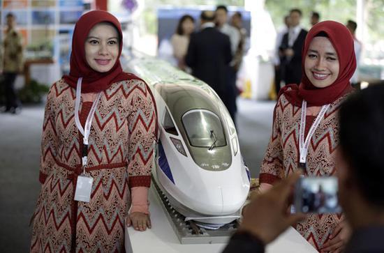 2016年1月21日,在印度尼西亚西爪哇省瓦利尼,两名印尼妇女在开工仪式上与高铁列车模型合影。新华社/美联